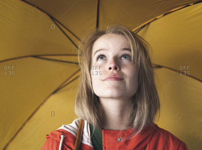 Close-up of young woman with yellow umbrella looking up in city