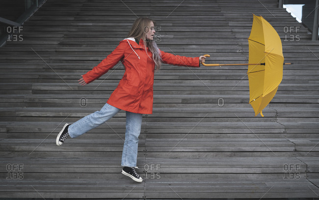 Playful young woman holding umbrella while dancing on steps