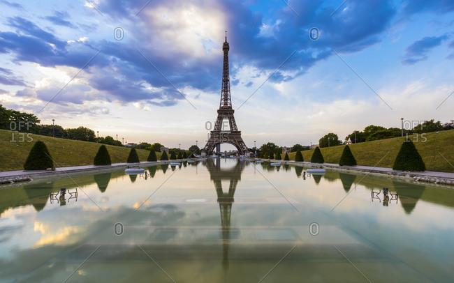 Eiffel Tower by Seine river against blue sky at sunset- Paris- France
