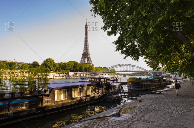 Eiffel Tower by Seine river against clear blue sky during sunrise- Paris- France
