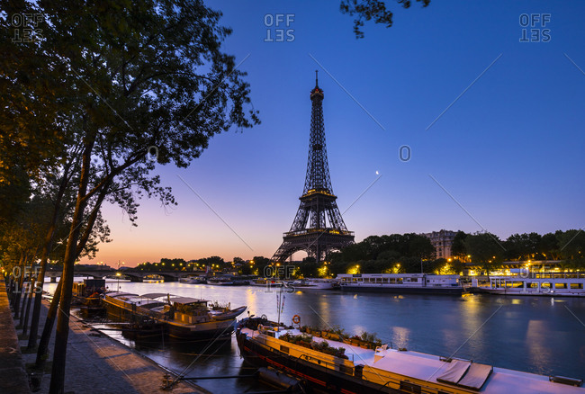 June 28, 2019: Eiffel Tower by Seine river against clear blue sky at sunset- Paris- France