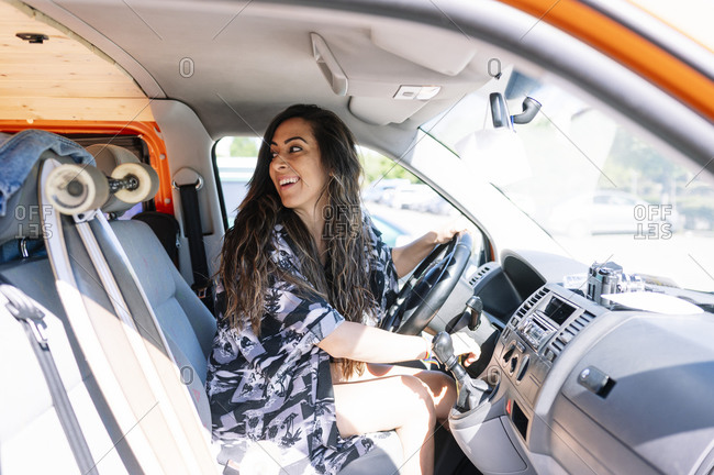 Young woman driving camper with skateboard on passenger seat