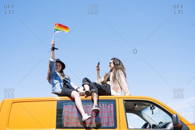 Two women sitting on roof of van- waving pride flag