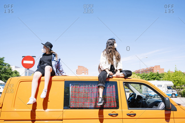 Two women sitting on roof of van- wearing protective face masks