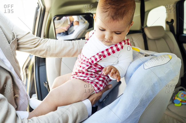 Father fastening baby boy sitting in child's seat in a car