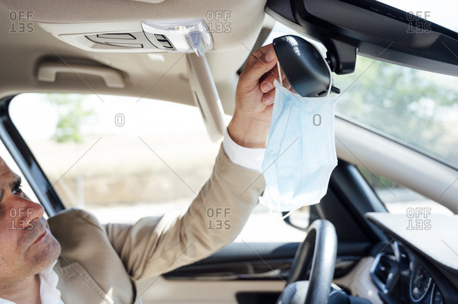Portrait of man in car taking off his protective mask