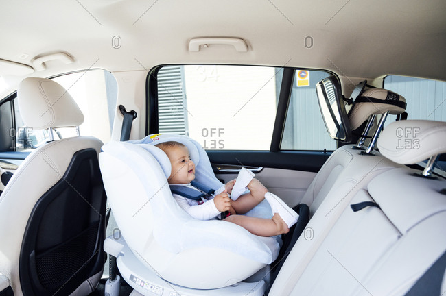 Baby boy sitting in child's seat and looking in mirror in a car
