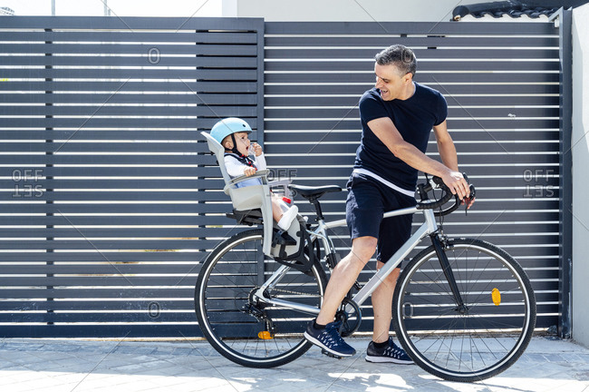 Father with son sitting in safety seat of bicycle