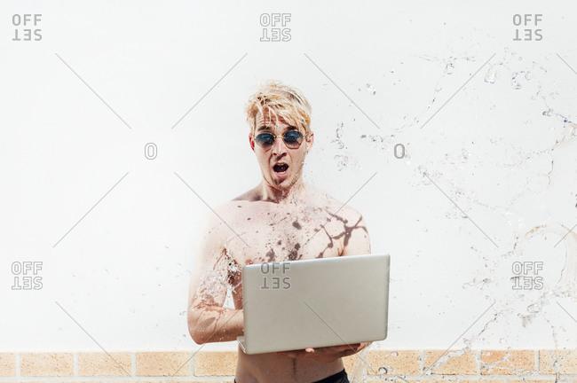 Water splashing on shirtless man using laptop while standing against wall