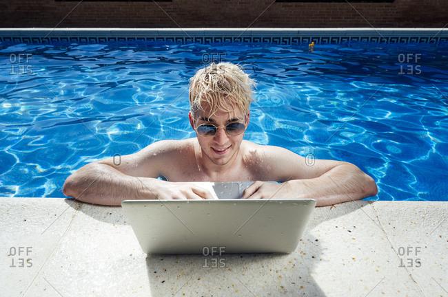 Shirtless handsome man wearing sunglasses using laptop at poolside