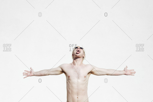 Shirtless young man with arms outstretched and mouth open standing against white wall