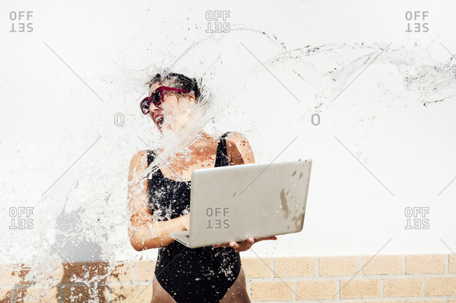 Water splashing on mid adult woman using laptop while standing against wall