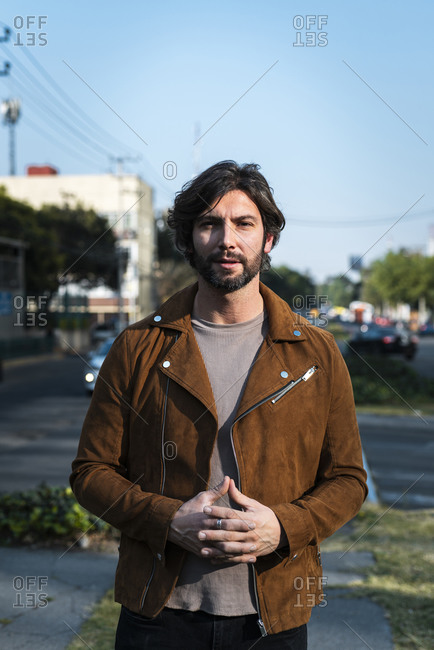 Handsome man wearing jacket standing on street against clear sky in city