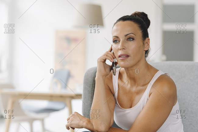 Close-up of businesswoman talking over smart phone while sitting on sofa at home office
