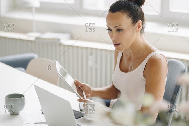Businesswoman holding digital tablet looking at laptop on desk in loft