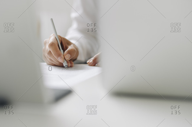 Close-up of female entrepreneur writing on paper at desk in home office