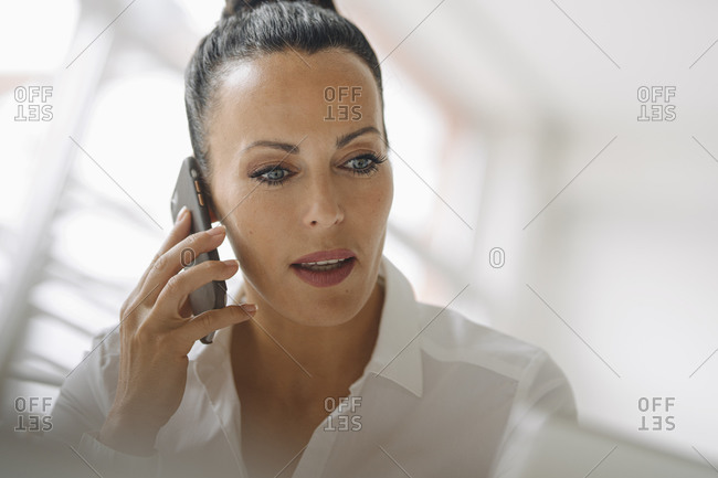 Close-up of businesswoman talking over smart phone in home office