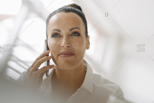 Close-up of smiling businesswoman talking over smart phone looking away in home office