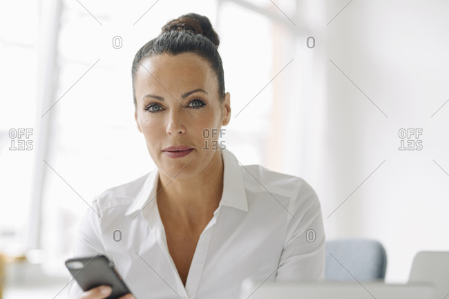 Confident businesswoman using smart phone while sitting in home office