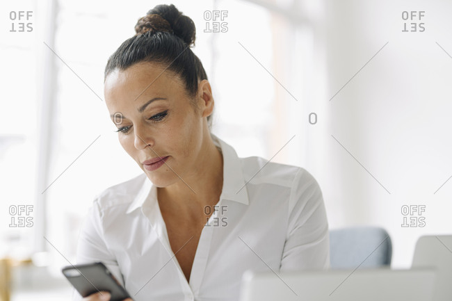 Confident female entrepreneur using smart phone while sitting in home office