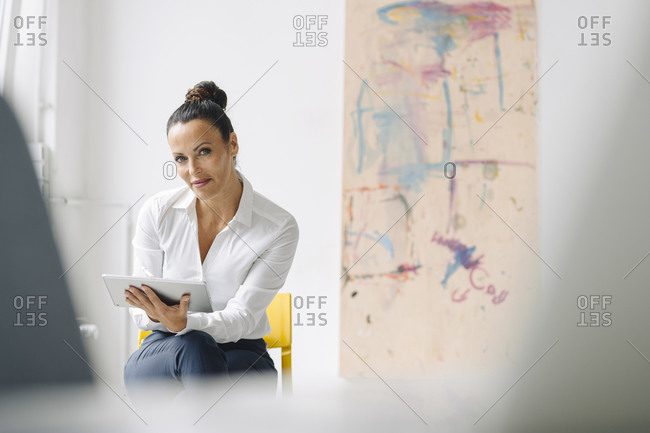 Confident businesswoman using digital tablet while sitting on chair in home office