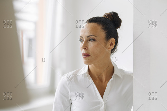 Close-up of thoughtful businesswoman standing by wall in home office