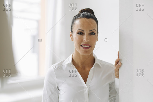 Close-up of smiling businesswoman standing by wall in home office