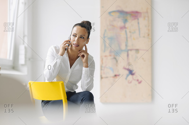 Businesswoman talking over smart phone while sitting on chair in home office
