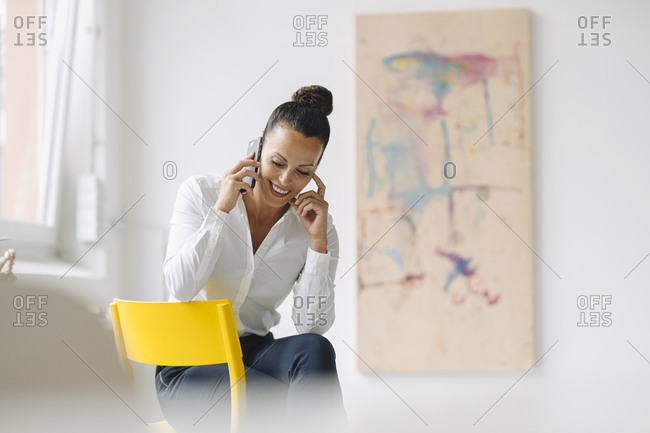 Smiling businesswoman talking over smart phone while sitting on chair in home office