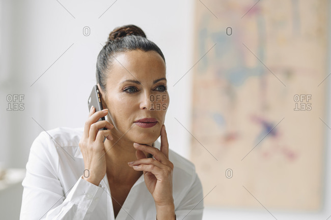 Close-up of businesswoman talking over mobile phone looking away in home office