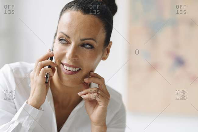 Close-up of smiling businesswoman talking over mobile phone looking away in home office
