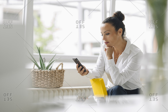 Female entrepreneur using mobile phone while sitting by window in home office