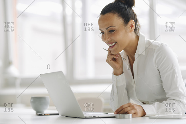 Smiling businesswoman using laptop on desk in home office