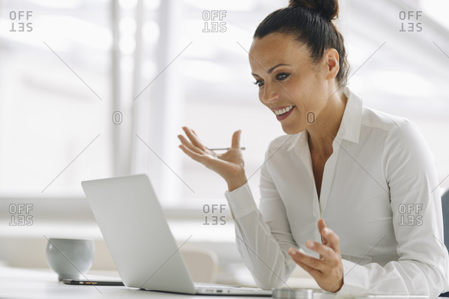 Smiling female entrepreneur using laptop on desk in home office