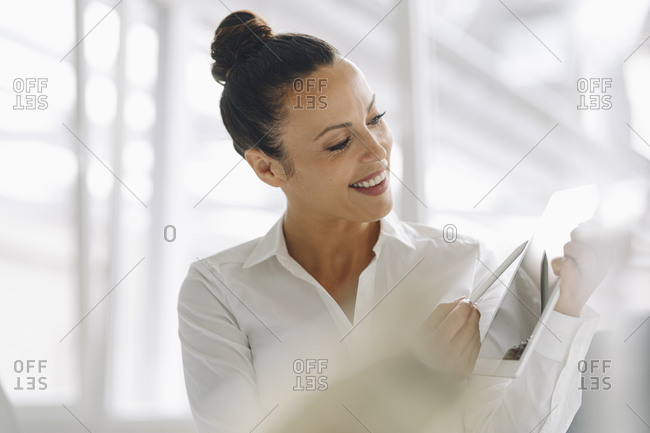 Close-up of smiling businesswoman using digital tablet in home office