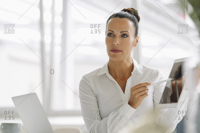 Close-up of confident businesswoman holding digital tablet while sitting in home office