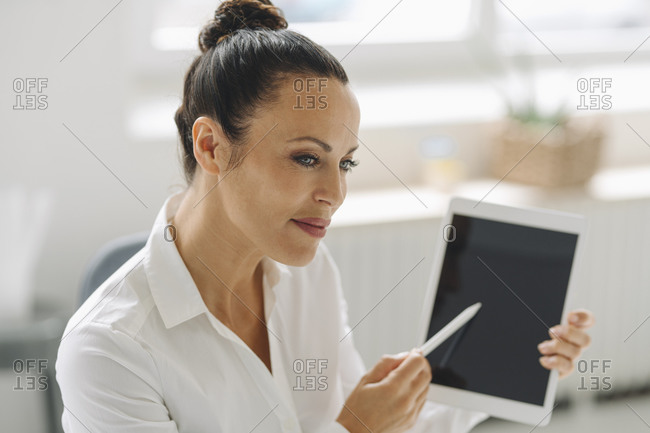Close-up of female entrepreneur holding digital tablet looking away in home office