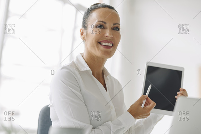 Close-up of smiling entrepreneur holding digital tablet looking away in home office
