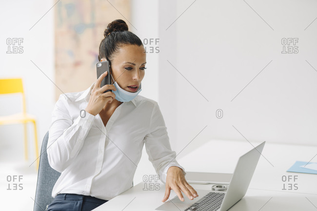 Businesswoman wearing mask talking over smart phone while using laptop on desk in home office