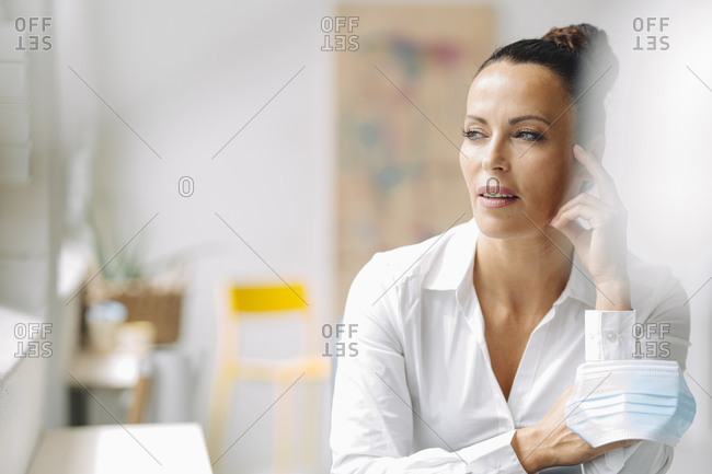 Thoughtful businesswoman holding mask looking away while sitting in home office