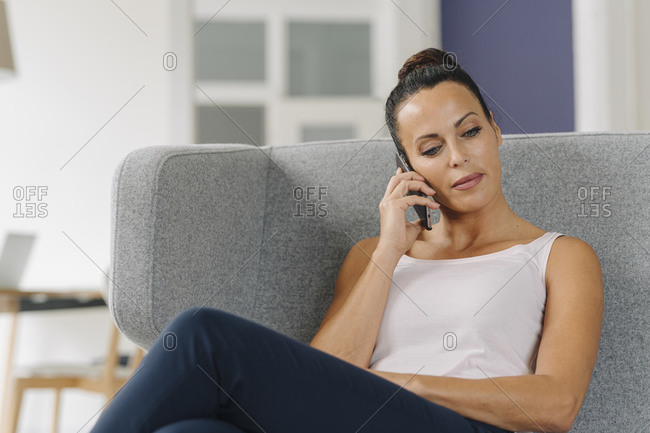 Businesswoman talking over smart phone while relaxing on sofa at home