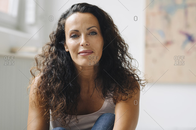 Close-up of beautiful woman with wavy hair sitting at home