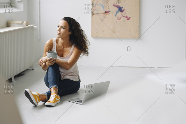 Thoughtful woman holding coffee mug while sitting with laptop on floor at home
