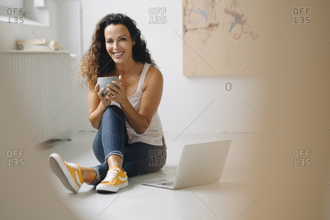 Smiling beautiful woman holding coffee mug while using laptop on floor at home
