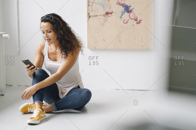 Mid adult woman using smart phone while sitting on floor at home
