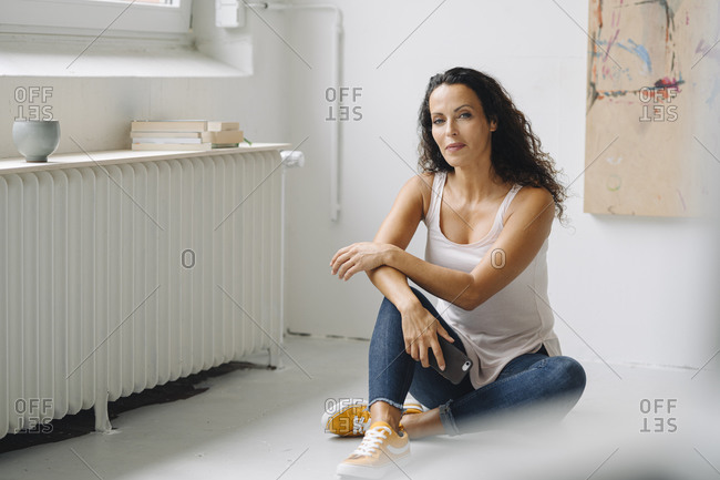 Confident mid adult woman holding smart phone sitting on floor in loft apartment