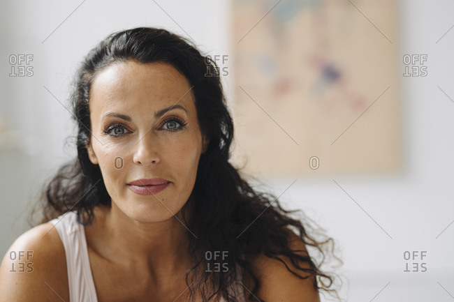 Close-up of smiling beautiful woman with wavy hair sitting in loft at home