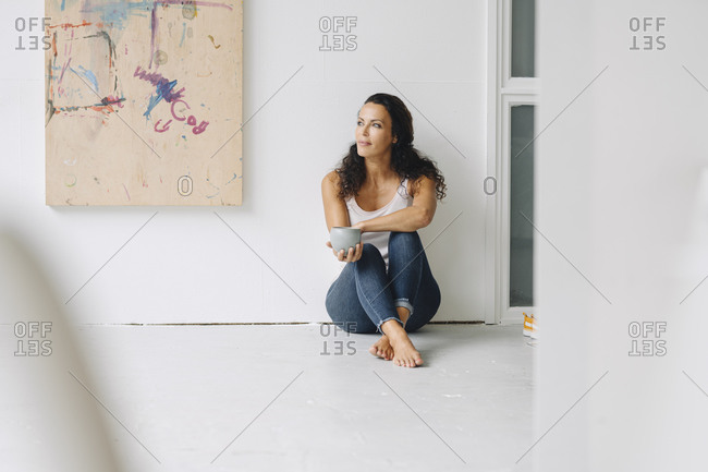 Woman holding coffee mug contemplating while sitting on floor against wall in loft