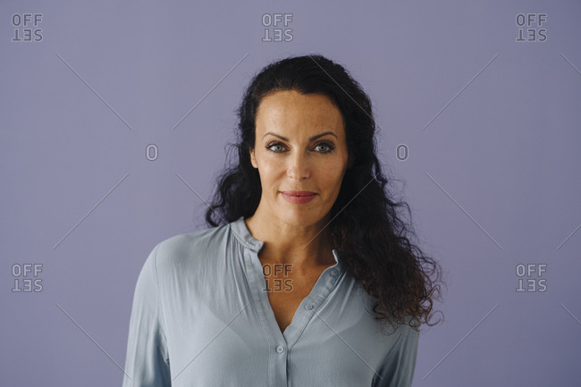 Confident beautiful woman with wavy hair standing against purple background