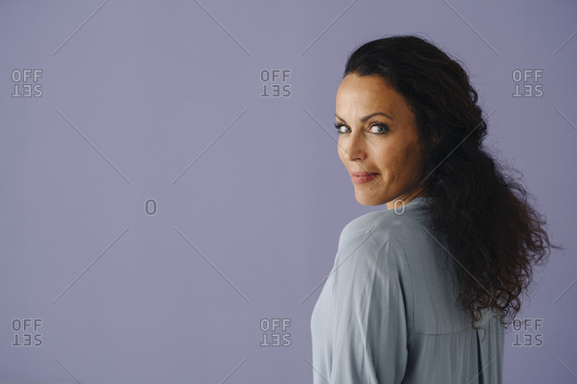 Confident woman with wavy hair standing against purple background